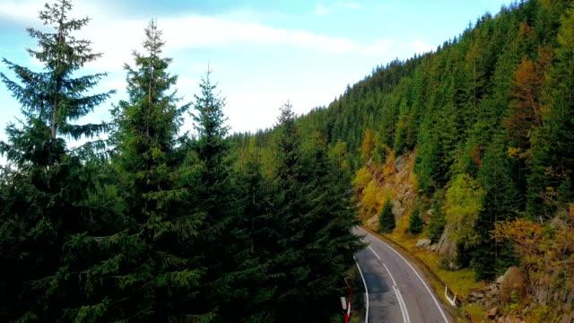 Carretera de montaña y vista en colinas boscosas. Rodaje aéreo