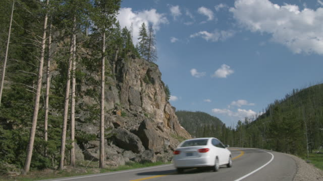 WS Mountain highway with car passing by / Yellowstone, Wyoming, USA