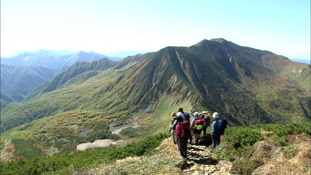 Mountain hikers admire view from ridge of Mt. Horoshiri