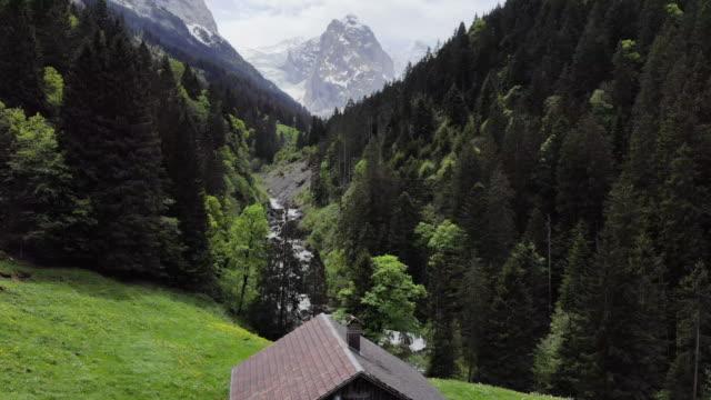 berghütte blickt auf alpine stream und schneebedeckten gipfel - alpen stock-videos und b-roll-filmmaterial