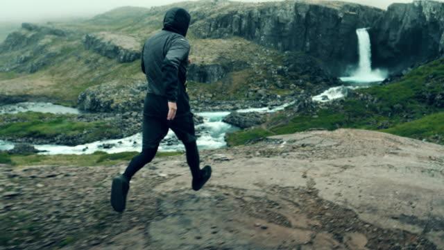 vidéos et rushes de montagne de jogging. homme qui court le long du sentier de montagne. cascade en arrière-plan - chute d'eau