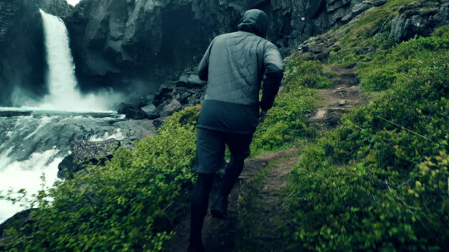 berg, joggen. mann läuft entlang bergweg. wasserfall im hintergrund - island stock-videos und b-roll-filmmaterial