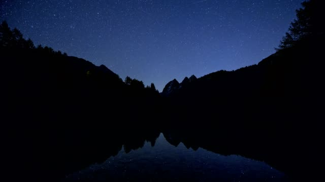 mountain lake at night with starry sky and road traffic, preda, lake palquognasee, lai da palquogna, albula-pass, grisons, switzerland, european alps - schweizer alpen stock-videos und b-roll-filmmaterial