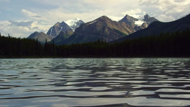 vídeos y material grabado en eventos de stock de un lago de montaña suavemente ondula con un bosque y las montañas rocosas canadienses en el fondo en el parque nacional jasper en alberta, canadá - paisaje espectacular