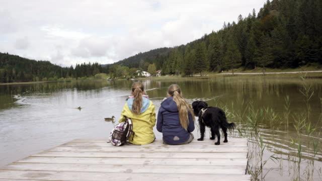 mountain lake, girls sitting on lake, dog, from behind, pan shot