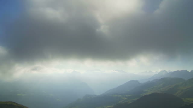 mountain landscape, sun peaking through clouds