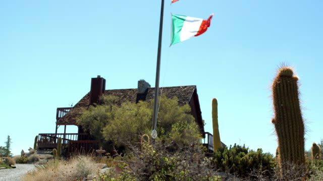 ts mountain lodge house featuring pitched roof and two levels of balconies,a flag of italy on pole flapping in the wind - italian culture stock-videos und b-roll-filmmaterial