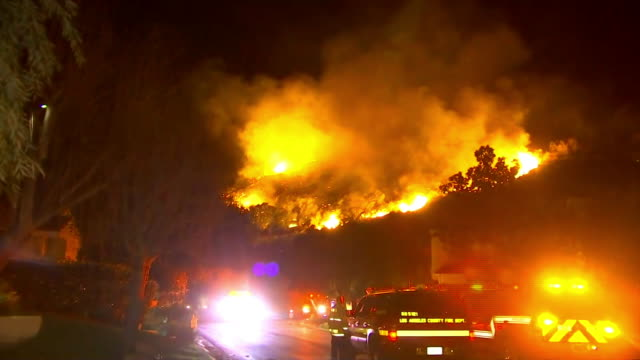 mountain on fire in westlake village california with emergency vehicles on the road in the neighborhood nearby - westlake village california stock videos & royalty-free footage