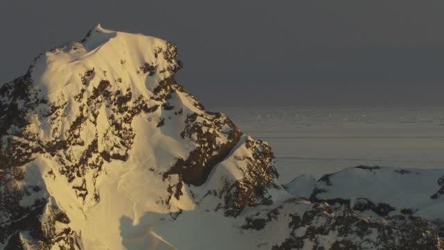 mountain peak w/ snow exposed volcanic rock in partial sunlight flat snowy landscape bg nordic north atlantic ocean island european union no people - subtraction stock videos & royalty-free footage