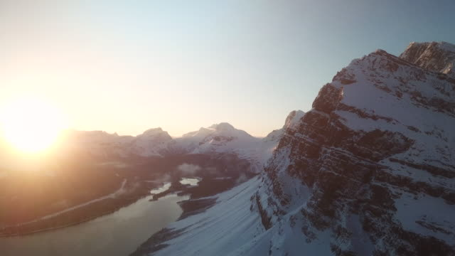 mountain peak with sunrise:aerial view - snowcapped mountain stock videos & royalty-free footage