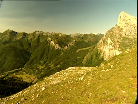 mountain peaks and forest area pan left to vast mountain ranges with a green valley below - eskapismus stock-videos und b-roll-filmmaterial