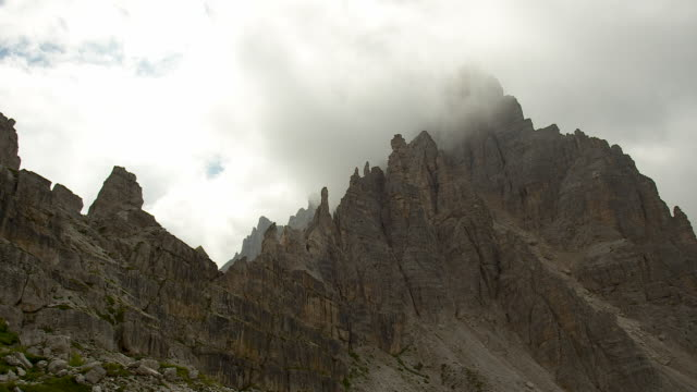 Mountain peaks rise into the cloudy sky, south tyrol alps