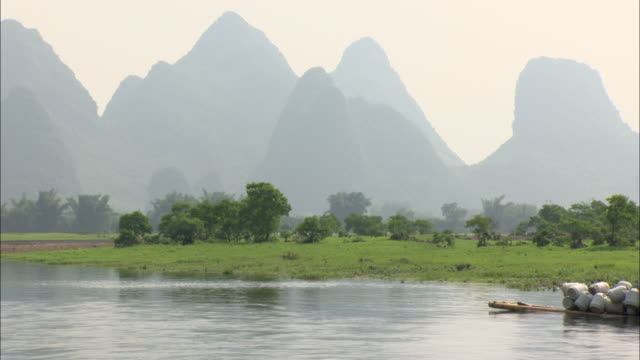 vídeos de stock e filmes b-roll de ws side pov mountain range by li river, farmers on motorboat, guilin, guangxi zhuang autonomous region, china - barco