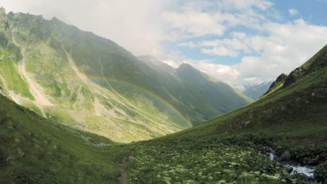 vidéos et rushes de chaîne de montagnes du caucase. belle prairie de vallée avec l'arc-en-ciel - mountain range