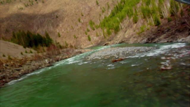 SLO MO, LOW AERIAL, Mountain river valley, Whitefish, Montana, USA