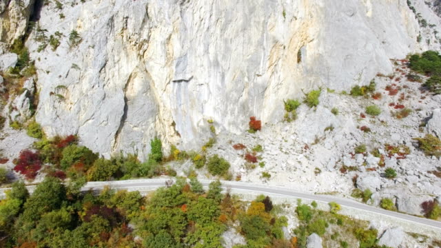 AERIAL: Mountain road at the foot of mountain rocks