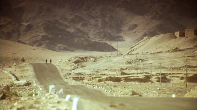 ws, mountain road, two people walking in distance, ladakh, jammu and kashmir, india - jammu e kashmir video stock e b–roll