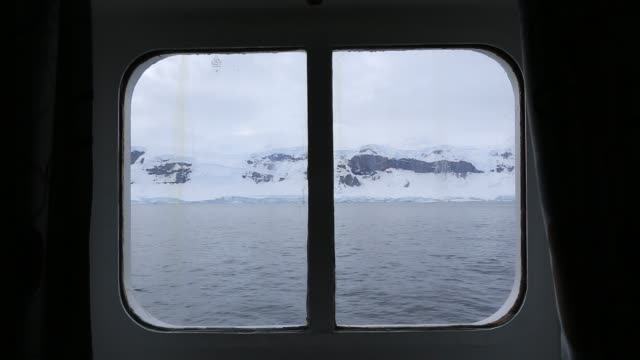 mountain scenery in fournier bay in the palmer archipelago, antarctica from the cabin window of an ice strengthened expedition cruise ship. - bay window stock videos & royalty-free footage