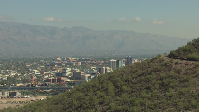 WS AERIAL Mountain side to reveal downtown buildings / Tucson, Arizona, United States