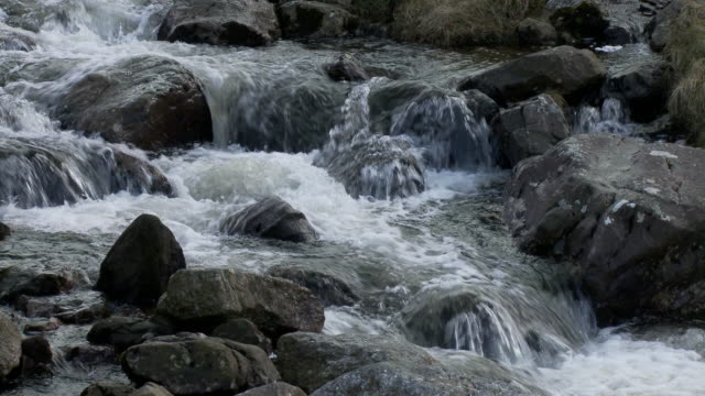 Mountain stream or river: Tilt up from water flowing over rocks and boulders to small bridge over river, Brecon Beacons, Wales