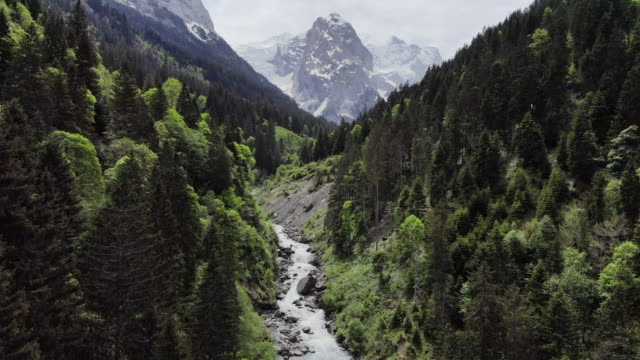 mountain stream rushes with glacial melt in swiss alps - snowcapped mountain stock videos & royalty-free footage