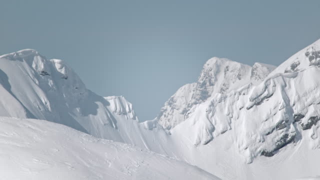SLO MO Mountain tops covered in snow on a sunny day
