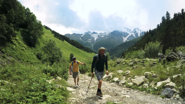 Mountain trekking. Backpackers walking on a caucasian trails