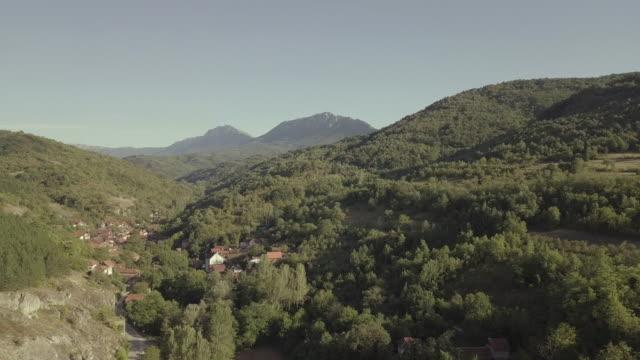 vídeos y material grabado en eventos de stock de aldea de la montaña desde el aire 4k - casa de ladrillo