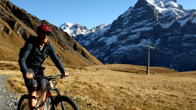 Mountainbiker ascends slope with dramatic view behind