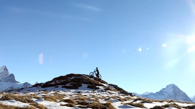 mountainbiker steigt hang mit dramatischen blick hinter - mountainbiking stock-videos und b-roll-filmmaterial