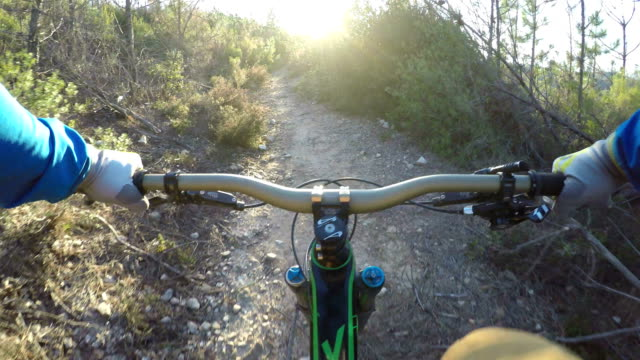 Mountain-biker ascends sunny Mediterranean trail
