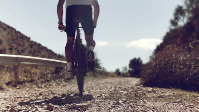 mountainbiker climbs on unpaved track in sun. - surface level stock videos & royalty-free footage