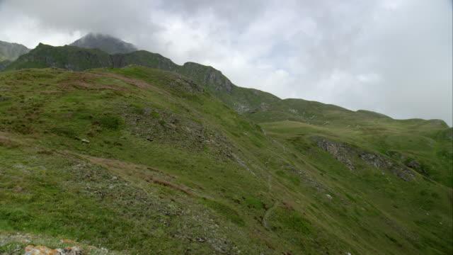 vídeos y material grabado en eventos de stock de mountainbiker conducción a través de un terreno de los alpes - mountain bike