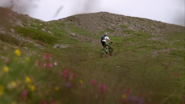 Mountainbiker conducción a través de un terreno de los Alpes