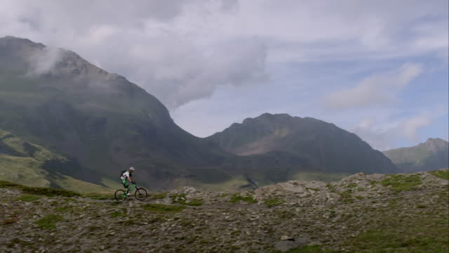 Mountainbiker driving through alpine terrain