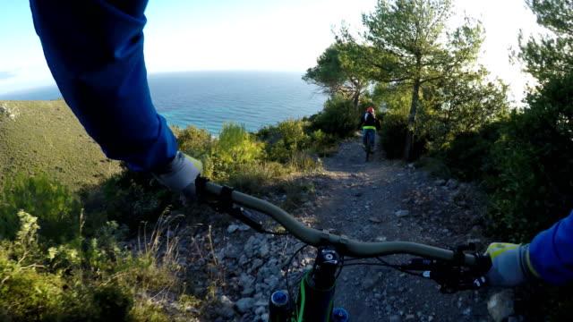 stockvideo's en b-roll-footage met mountainbiker volgt metgezel onderaan steile mediterrane trail - mountainbike