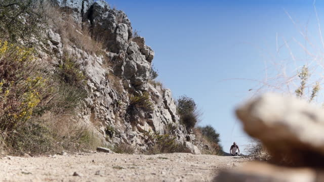 Mountainbiker going downhill on rocky road