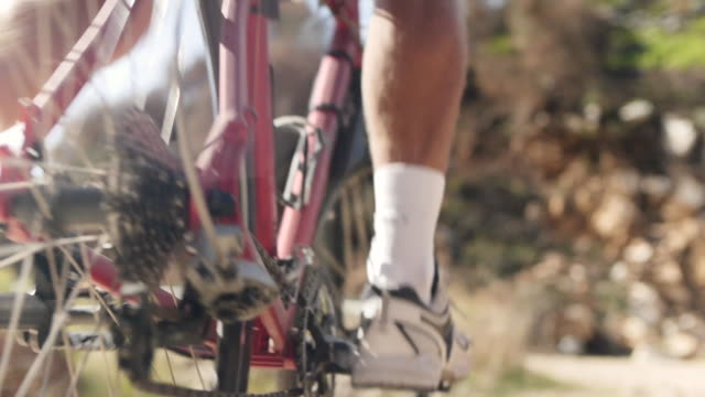 Mountainbiker going uphill on rocky road
