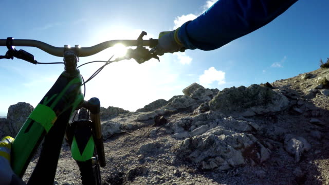 Mountain-biker pushes bike up to hilltop view