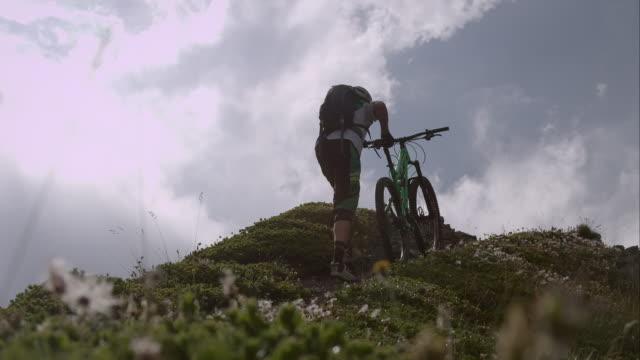 vídeos de stock, filmes e b-roll de mountainbiker empurrando sua bicicleta para cima - colina acima
