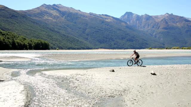 Mountain-biker rides along mountain riverbank