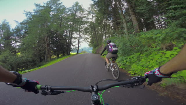POV mountainbiking action: pedaling with a woman on the Alps