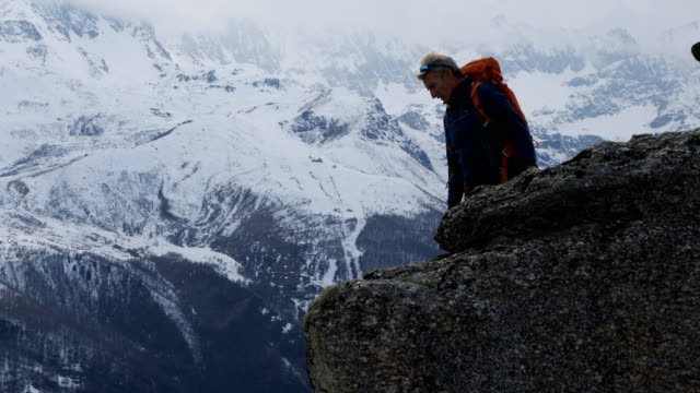mountaineer abseils (rappels) from rocky ledge - courage stock videos & royalty-free footage