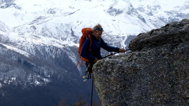 mountaineer abseils (rappels) from rocky ledge - abseiling stock videos & royalty-free footage
