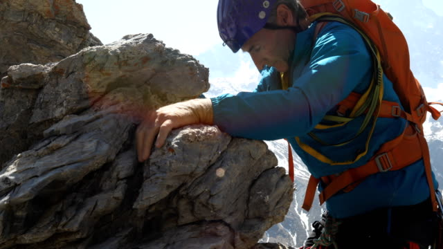 mountaineer approaches summit of high mountain pinnacle with dramatic alpine view behind - conquering adversity stock videos & royalty-free footage