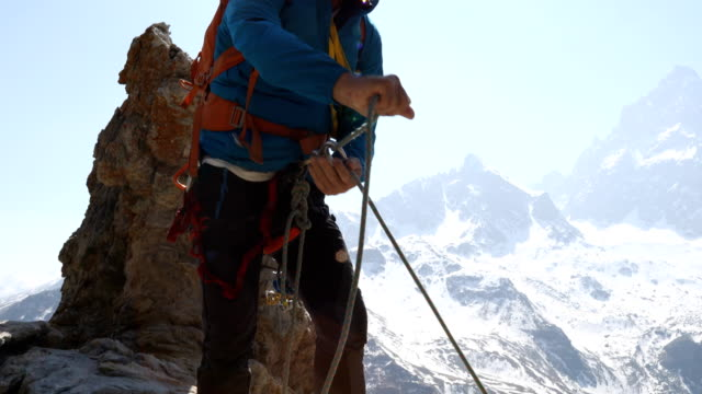 mountaineer approaches summit of high mountain pinnacle with dramatic alpine view behind - rope stock videos & royalty-free footage