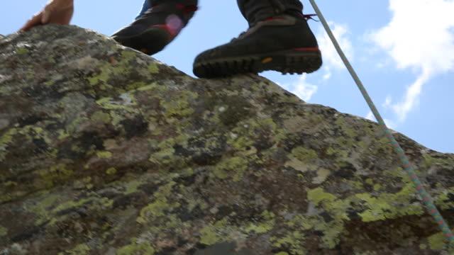 vidéos et rushes de mountaineer ascends mountain ridge, coils rope - un seul homme d'âge moyen