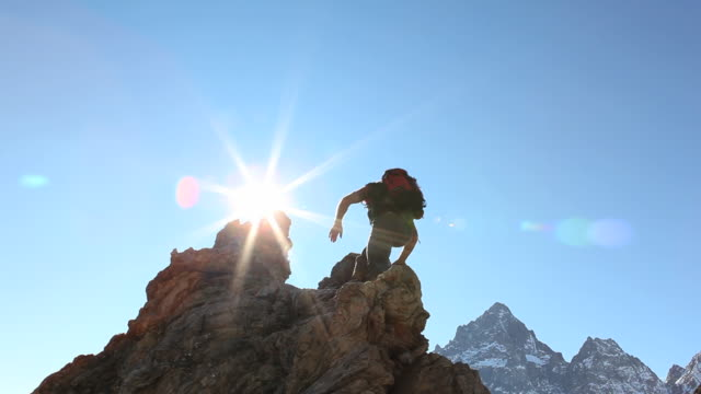 Mountaineer ascends narrow ridge above snowy mountains