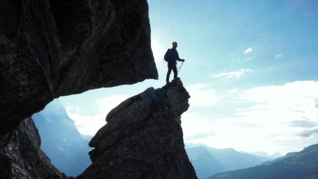 Mountaineer ascends pinnacle above distant mountains and throws rope