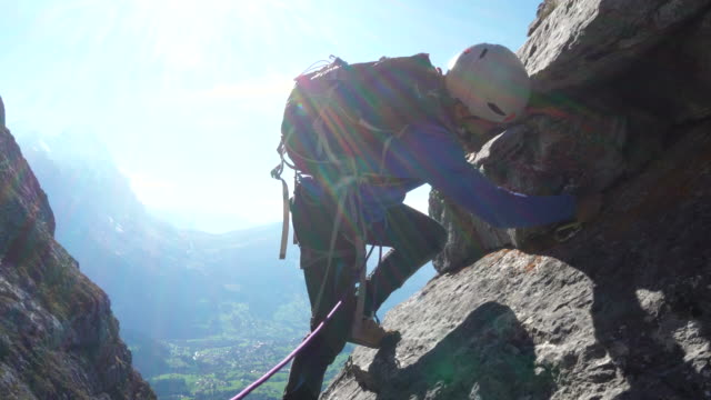 Mountaineer ascends pinnacle above distant mountains
